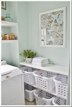 Laundry room sorting station. Love the sea glass color of the room and the framed fabric idea.