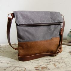 The Waxed Canvas & Leather Foldover Day Bag is easy and breezy for everyday. Made of durable and water resistant waxed canvas and distressed brown leather,giving the bag a rugged sturdiness for years of abuse and enjoyment. Our slate waxed canvas is our most popular color.  Features: About 10.