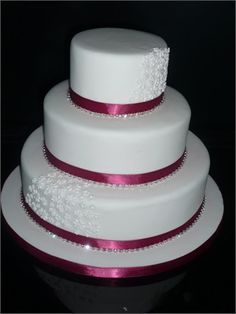 Three tier stacked cake trimmed with burgundy ribbon and diamante trim. The top and bottom tiers are decorated with little blossoms.