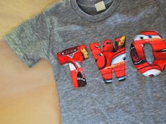 I designed this tee with my two year old lilttle guy in mind. He can't get enough of Cars 2! This cool red fabric features the Cars movie favorite...Lightning McQueen! The print fabric is securely sewn to an Alternative Apparel eco-grey heather tee. If you prefer a different color tee I can also do eco black, eco brown or white burnout. Please be sure to indicate color choice and size when ordering. I have other Cars themed tees in my shop if you would like to take a look :) ***lil thr... Car Themed Parties, Cars Birthday Parties, 2nd Birthday, Birthday Ideas, Happy Birthday, Lightning Mcqueen Party, Lightning Mcqueen Birthday Cake, Cars Birthday Invitations, Disney Cars Birthday