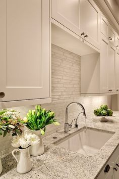 Lovely creamy white kitchen design with shaker kitchen cabinets painted Benjamin Moore White Dove, Kashmir White Granite counter tops, polished nickel modern faucet and Vetro Neutra Listello Sfalsato Glass Mosaic- Bianco tiles backsplash. Benjamin Moore White Dove