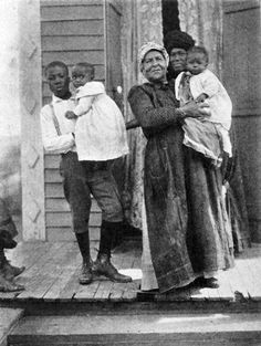 Three generations of a Louisiana family; Grandmother can only speak Creole French; mother speaks French and English; boy only speaks English. Photo was taken in 1910.