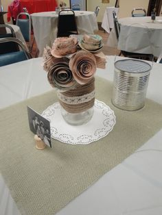 Anniversary party centerpieces: wood spool with photo, rolled paper flowers and punched tin can lantern