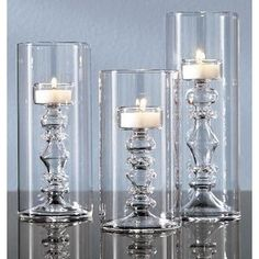 DIY Centerpiece Ideas: Place candle holders in cylinder vases to create not only a unique centerpiece but a more stable one as well that won't easily topple over.