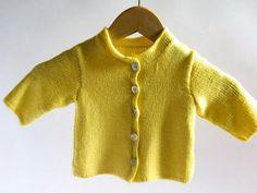 Chaqueta de punto de mangas largas de color amarillo cerrada con botones de nácar. Esta tejida y cosida a mano con hilo especial para bebés de tacto muy suave y un poco elástico.  Puedes combinarla...
