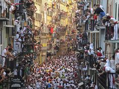 Pedro Armestre—AFP/Getty Images July People standing on balconies look at participants as they run in front of Alcurrucen's bulls during the first bull run of the San Fermin Festival in Pamplona, northern Spain. San Fermin Pamplona, Running Of The Bulls, Pictures Of The Week, Places To See, Cool Photos, Amazing Pictures, Tourism, Beautiful Places, Amazing Places