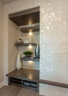 Modern dark gray EVRGRN Rok engineered wood shelves in a staggered pattern with integrated fireplace mantle accent in the same material. Modern white textured square fireplace tile