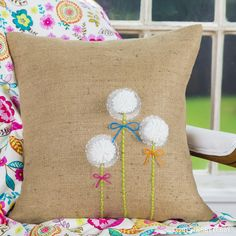 Spruce up an everyday burlap pillow with handmade pom-poms and DIY art.