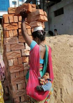 This image showing a hardworking mother in India carrying six bricks on her head while bal. We Are The World, People Around The World, Around The Worlds, Mundo Cruel, Kinder In Not, Amazing India, Working Woman, Working People, Working Mother