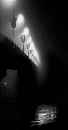 Black and white photo of the glow of a row of lamplights on the pier's edge.