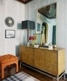 Midcentury console table with lamp, leaning mirror, vase of flowers, and tufted stool