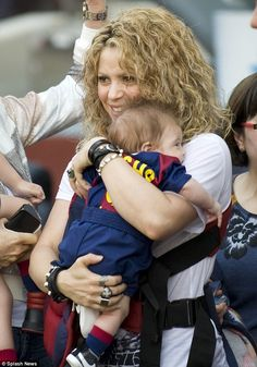 Accessorised: Shakira showed off her edgy arm candy and finger rings while holding her lit...