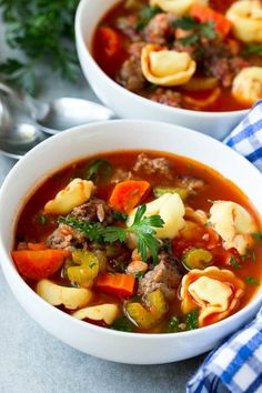A bowl full of tortellini soup with sausage and vegetables.