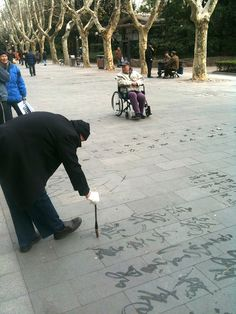 A retired man practicing his calligraphy on the ground of a park. He uses water to write and by the time he finishes his last character of a poem, the first character may already become traceless. So he can forget what he has done and keeps doing the next - a way of both physical and mental exercise.