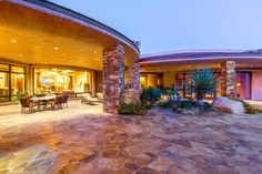 The exterior of the home is breathtaking with a beautiful natural backdrop, an infinity edge pool, expansive covered patios, stacked stone, multiple fireplaces and a top-of-the-line outdoor kitchen. There is also an additional pool house that features a game room with a full bar.