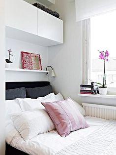 Repisa blanca sobre la cama con lámpara de clip, un cuadro y una maceta con flores; sobre ésta repisa otra más grande y cerrada que sirve para almacenar cosas.