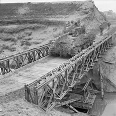 A heavily camouflaged Sherman tank crosses a Bailey bridge over the River…
