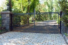 A very clean, streamlined driveway gate style is softened by the interesting circle details. Simple iron designs like this tend to be less expensive than ornate iron styles. Gate designed and installed by Tri State Gate in Bedford Hills, NY. Wrought Iron Driveway Gates, Driveway Entrance, Front Gates, Entrance Gates, House Fence Design, Bedford Hills, Steel Gate Design, Brick Columns, Farm Gate