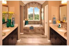 Matching sinks flank an elegant tub framed by a graceful, arched ceiling. The Cartwright plan, built by Drees Homes, in the Kendall Wood community. Carmel, IN.