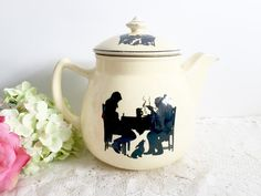 This listing is for a pretty vintage teapot, the back stamp says Pantry Bak-in by Ware Crooksville Teapot. It has a silhouette design of a tavern on both sides. The silhouette design has a dramatic black outline of two men sitting at a table with a steaming plate of food and a beer stein, and a small dog below. The teapot is a light yellow color with black trim.  Measures 9 1/4 long and approximately 7 3/4 high.  Some light vintage wear, please look at photos for reference. No crack...