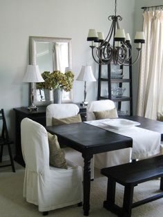 black table, white slipcovered chairs, linen/burlap throw pillows.  love.