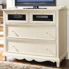 """Two-drawer media console with drop-front media compartments and a scalloped apron.Product: Media consoleConstruction Material: Wood, glass and cedarColor: LinenFeatures: Interchangeable wooden bead board or glass insert for drop frontCompartment has grommet hole, ventilation slot and power boxDistressed finish accentuates country designDimensions: 40"""" H x 46"""" W x 20"""" D"""