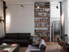 Na jednej ze ścian odsłonięto cegłę. By wnętrze było bardziej przytulne pomalowano ją na biało. Salon ociepla drewniana podłoga z desek oraz regał z drewna. Loftowy charakter podkreślają zaś reflektory umieszczone na długiej szynie oraz stalowa lodówka.