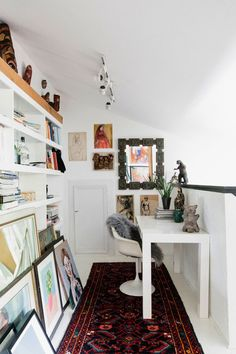 "A miniature office is wedged into the hallway across from the guest bedroom. A simple West Elm desk sits across from a wall of built-in shelving. ""I'm big on having that pop of modern—vintage or new—to keep spaces from looking to granny-ish,"" Aldridge says 