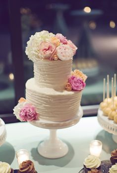 Brides.com: 32 of the Prettiest Floral Wedding Cakes. Two-tiered white wedding cake with fresh garden roses and hydrangeas, by Nashville Sweets.  See more romantic wedding cakes.