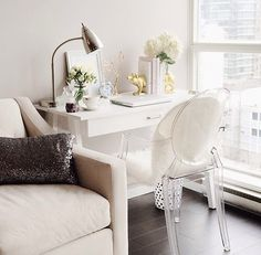 interior design white home office: Chic living room features corner office space with Target Threshold Basic Desk topped with CB2 Gold Pig Bookends paired with philippe starcke Ghost Chair sheep skin rug on chair next to floor to ceiling windows overlooking the city (dp)