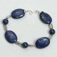 """Handmade gemstone lapis bracelet features a strand of large semi-precious lapis gemstone ovals, sterling silver accent beads, wire band, and lobster claw clasp. 8 1/2"""" in length. Add a necklace, penda"""