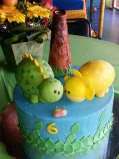 Un bello pastel de dinosaurios muy tierno para un hermoso niño con un pequeño volcán en medio.