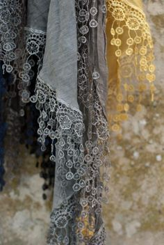 lacy fringed silk scarves against a lichen wall  photo Heather Ross