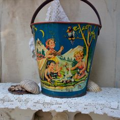 S.A.L.E. 15% off:  Vintage sand pail tin litho 1940s made in West Germany childrens toy camping scene day and night. $140.25, via Etsy.