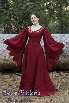 This gown, a transitional style between a cotehardie and a houppelande, is based on 15th century Italian sources. The dress is made of red wool and fully lined. The dress laces on the sides with hand sewn eyelets and hand made finger loop braid. The neckline is accented with gold silk and spangles, a precursor to modern sequins. The gown is worn here both with braided hair and with a decorated hat.