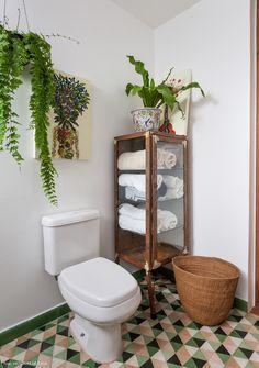 Banheiro com piso de ladrilho hidráulico, plantas pendentes e armário de farmácia.