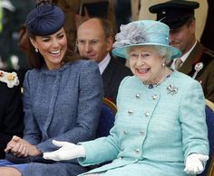 The Duchess of Cambridge laughs as Queen Elizabeth II gestures while they watch a children's sports event during a visit to Vernon Park