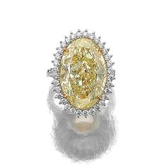 FANCY YELLOW DIAMOND RING. Claw-set with a fancy yellow oval diamond weighing 16.04 carats, the shoulders and frame set with brilliant-cut stones, mounted in yellow gold and platinum,