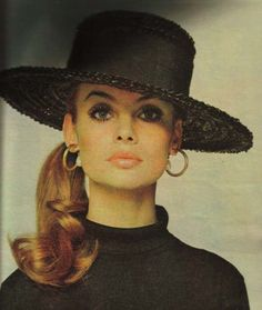 Jean Shrimpton, effortlessly chic in a black hat, side pony tail and gold hoop earrings