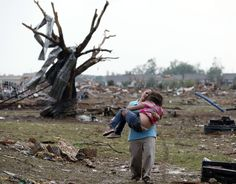 Tornado emergency in Moore, Okla. - A woman carries her child through a field near the collapsed Plaza Towers Elementary School. May 20