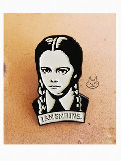 1.5 enamel pin / Wednesday Addams fan art  She meets your gaze and plainly states I AM SMILING  Designed by me and manufactured to my specs. You are purchasing the pin directly from the artist!  Great gift for people who hate smiling; or hate being told to smile even more