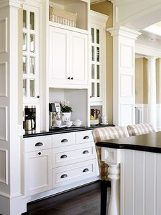 A built-in hutch with open counter space makes a fitting area for a beverage station. Ample cabinetry holds glassware and cups. A built-in coffeemaker and a freestanding espresso machine team up so a refill is always close at hand./