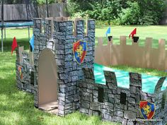 DIY castle out of cardboard and scene setter roll. Includes links to purchase accessories. Full medieval party ideas.