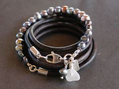Multi-wrap pearl and Leather bracelet with bright peacock pearls and silver charms.  A circle of 6-8mm Baroque pearls adorn this multi wrap bracelet. Finished with sea glass, pearl charm and recycled silver stamped bar charm. 4mm natural leather cord sterling end caps, and a oversized marquise clasp makes it easy to open and close. One of a kind style that circles the wrist 6 times at 43 inches. Ask for custom sizing.