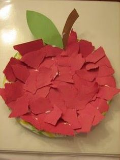 Making an apple from a small paper plate, torn red construction paper, and construction paper for the leaf and stem.