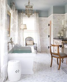 A ceramic garden stool makes for the perfect side table to your bathtub -- it's lightweight easy to move and easy to clean! See more of our favorite decorating ideas for classic white bathrooms over on our Style Guide!