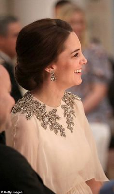 Tickled pink? Kate giggles away as she sits beside King Harald who escorted her into the d...