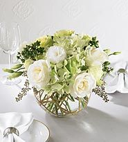 White and light green roses, gorgeous green hydrangea and green carnations along with white lisianthus accented with seeded eucalyptus and curly willow arranged in a clear glass bubble bowl.