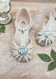 Reminiscent of the 1920's flapper, these shoes feature deco silver straps and canvas piping.  Circle detail at the center is finished with aurora borealis stone.  Buckle is fixed with velcro behind for easy on and off.  Youth sizes have a real buckle.  Includes a matching clip!