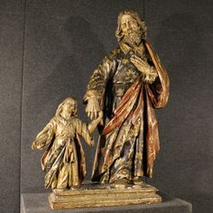 """Price: 7000€ French 18th century wooden sculpture. Work composed of two wooden sculptures with pedestal depicting """"St. Joseph and Jesus."""" Sculptures made by carved lacquered and painted wood. Lacquering realized during the 19th century, the sculpture in fact has some traces of the original gilding. It has several signs of aging and small lacks in the hands. In good state of conservation, despite the age. #antiques #antiquariato Visit our website www.parino.it"""